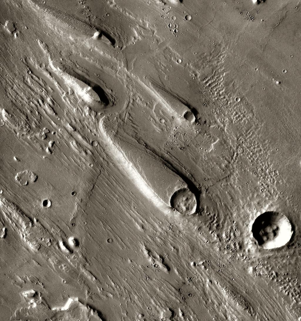 In Ares Vallis, teardrop mesas extend like pennants behind impact craters, where the raised rocky rims diverted the floods and protected the ground from erosion. This image is from NASA's Mars Odyssey, one of an 'All Star' set.