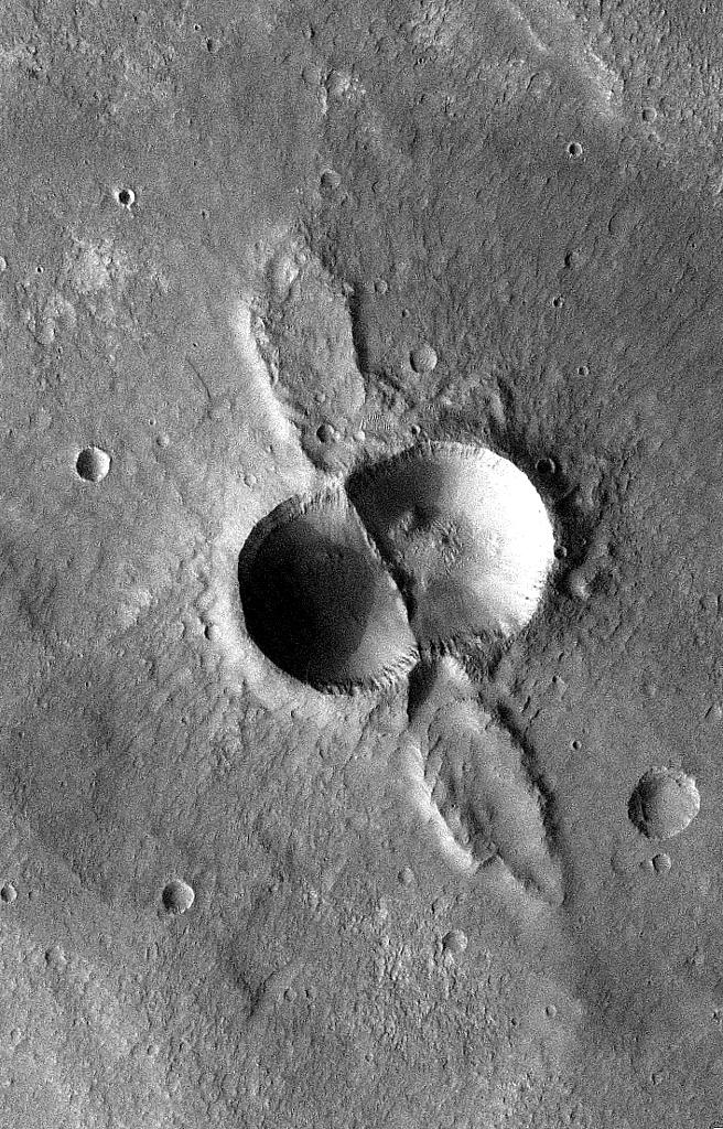 If a meteorite breaks in two shortly before hitting the ground, the typical bowl shape of a single impact crater becomes doubled. This image is from NASA's Mars Odyssey, one of an 'All Star' set.