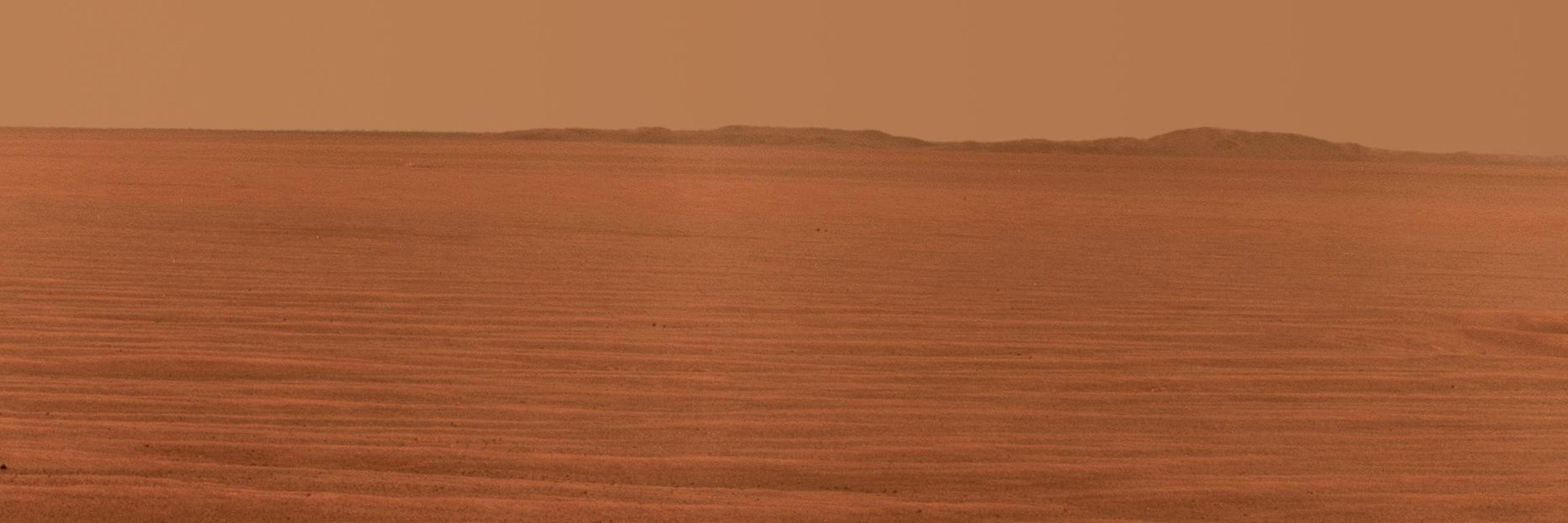 NASA's Mars Exploration Rover Opportunity used its panoramic camera to record this eastward horizon view. A portion of Endeavour Crater's eastern rim, in the distance, is visible over the Meridiani plain.