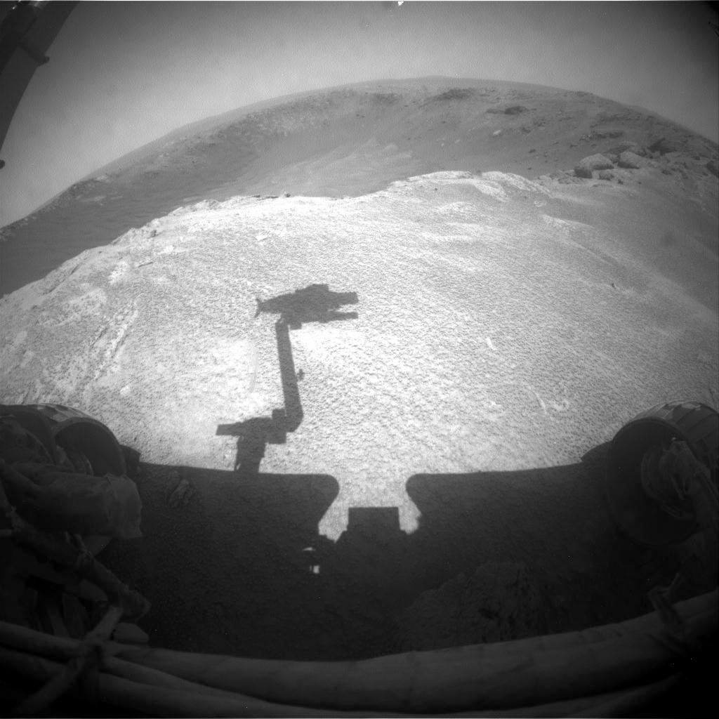 This image from NASA's Mars Rover Opportunity is from the edge of a football-field-size crater informally named 'Santa Maria.' The rover's upraised robotic arm, itself out of view, casts a dragon-shaped shadow in the foreground.