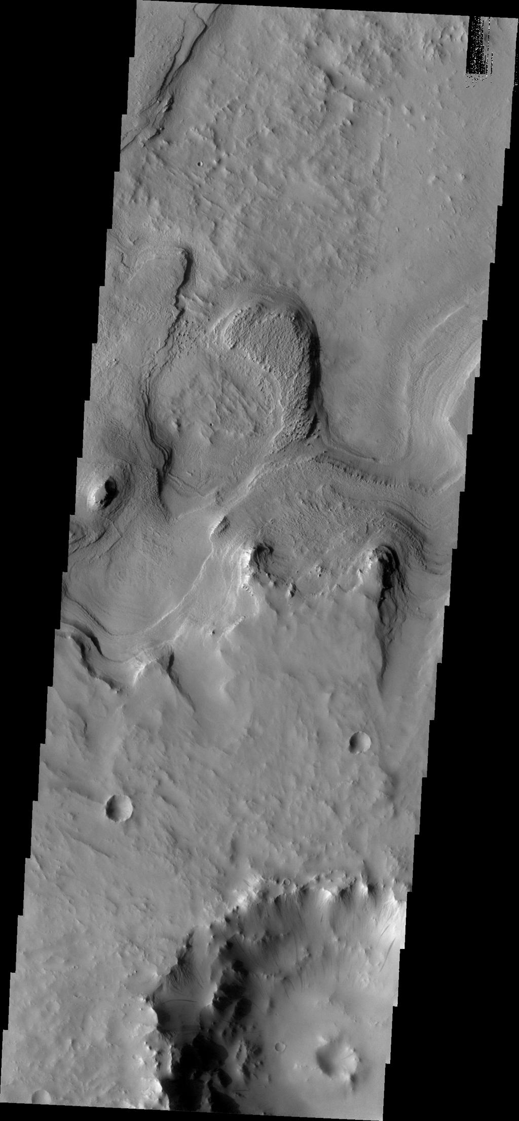 This image from NASA's Mars Odyssey shows layered material surrounding an unnamed crater in Terra Sabaea.