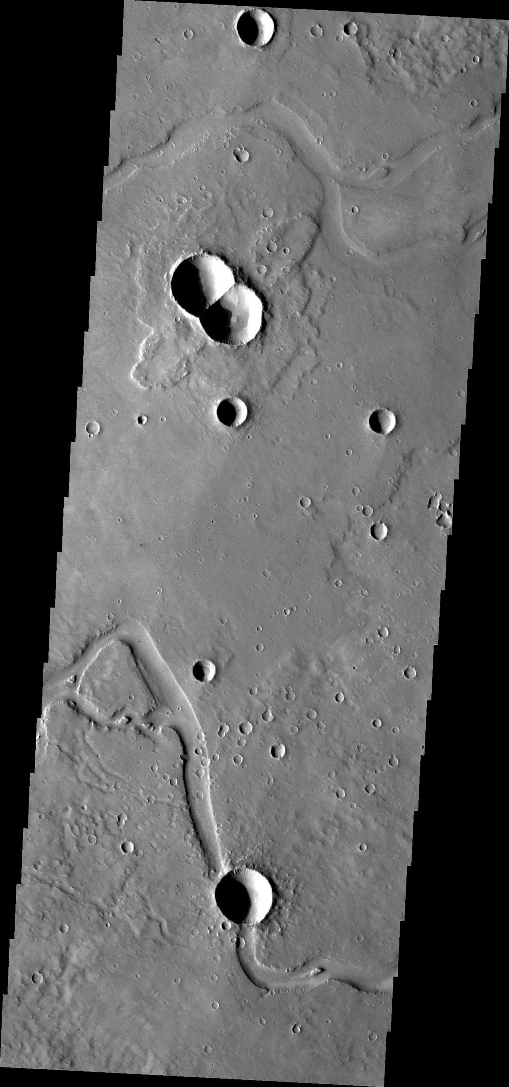 This image from NASA's Mars Odyssey is of a doublet crater located in Utopia Planitia, near the Elysium Volcanic region. Doublet craters are formed by simultaneous impact of a meteor that broke into two pieces prior to hitting the surface.