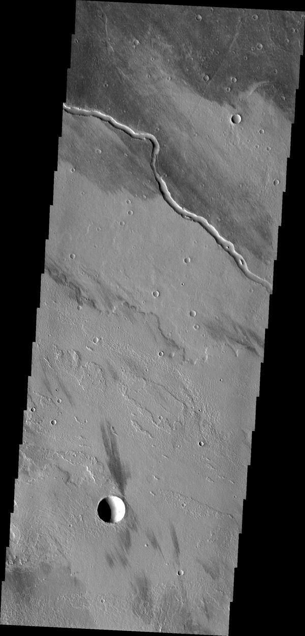 The channel seen in this image from NASA's Mars Odyssey is located within the Tharsis volcanic flows. It was most likely carved by the flow of molten lava.