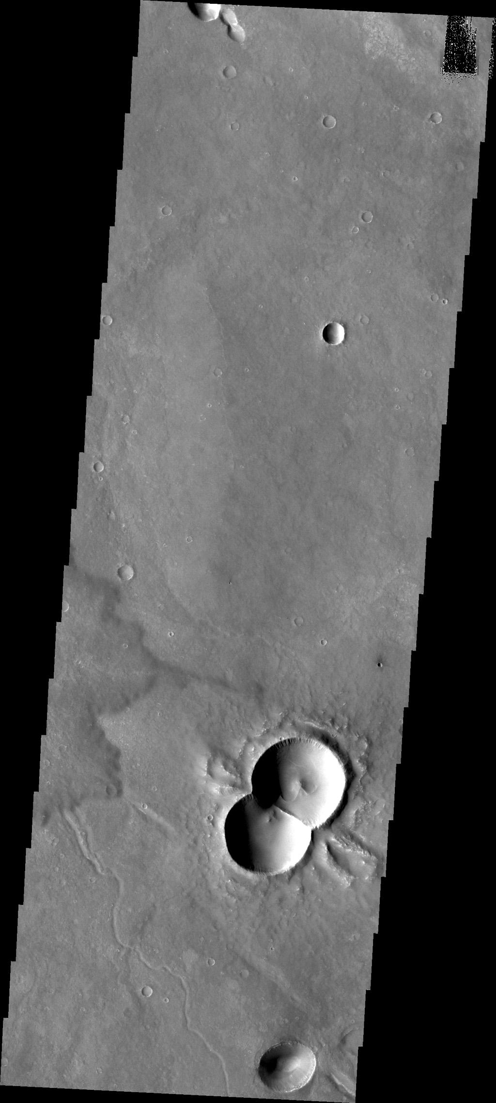 This doublet crater was formed when two meteorites impacted at the same time. The shock waves interact to form the straight central rim and the 'wings' of ejecta on the outside of the rims. This image is from NASA's Mars Odyssey.