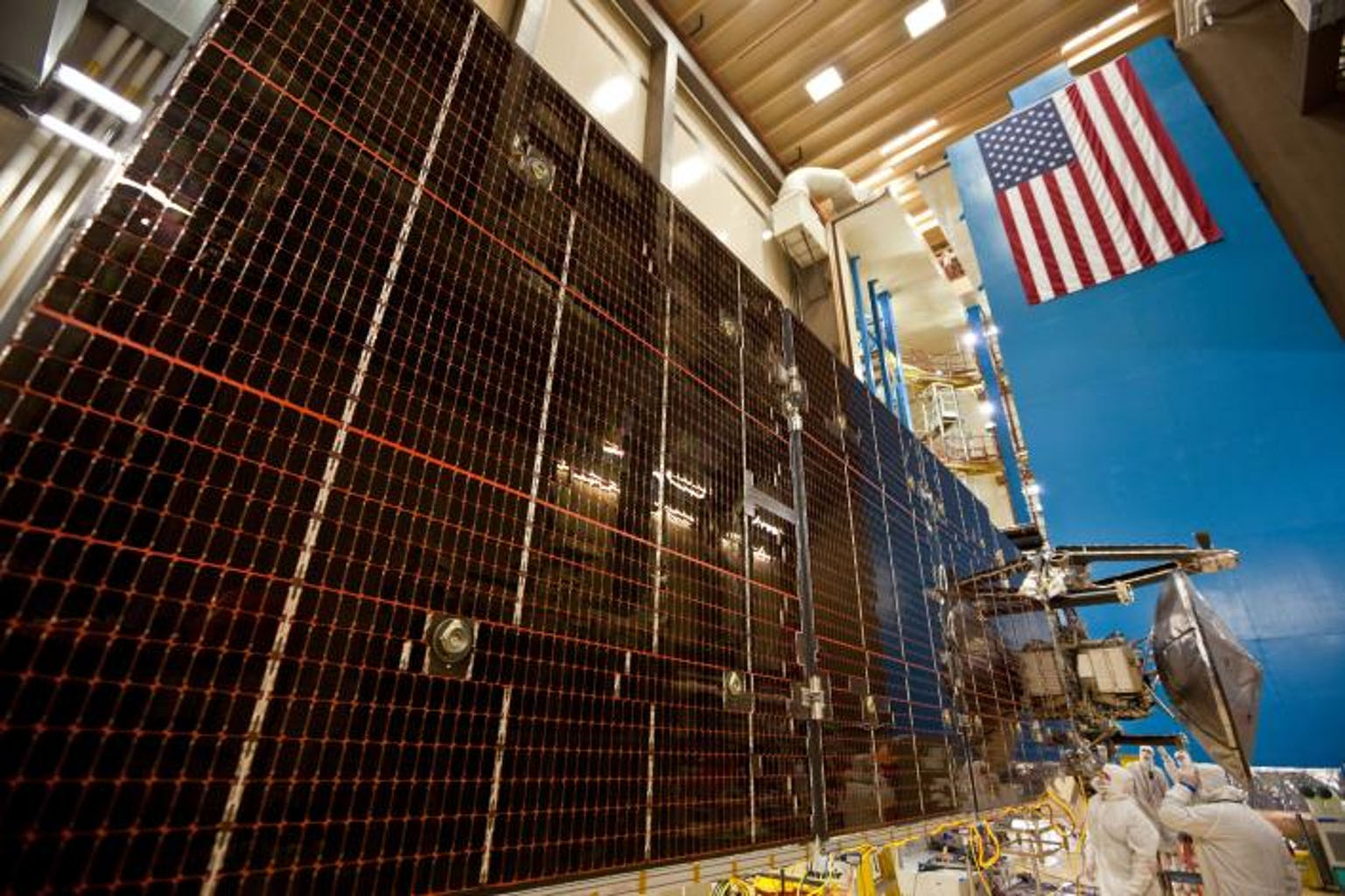 Technicians test the deployment of one of the three massive solar arrays that power NASA's Juno spacecraft.