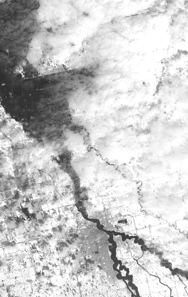 NASA's Terra spacecraft shows the annual spring thaw in the upper Midwest is underway. Snow-covered ground contrasts with the dark tones of water under broken cloud cover. Along the Red River in North Dakota, floodwaters are moving northward into Canada.