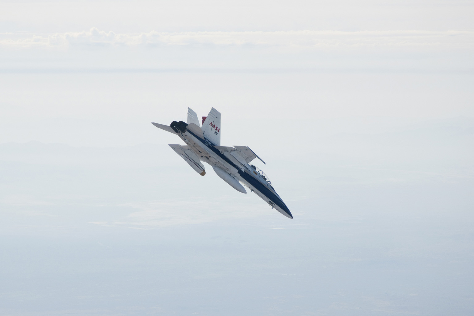 A NASA Dryden Flight Research Center F/A-18 852 aircraft makes a 40-degree dive during June 2011 flight tests of a Mars landing radar. A test model of the landing radar for NASA's Mars Science Laboratory mission is inside a pod under the left wing.