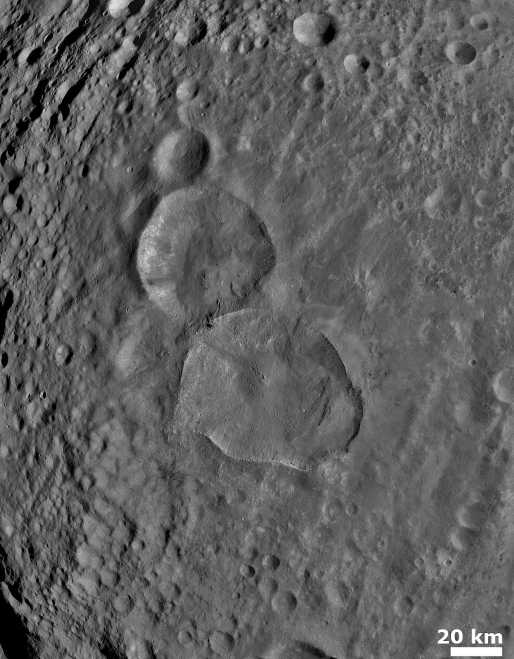 NASA's Dawn spacecraft obtained this image of two large, young craters on Vesta with its framing camera on August 6, 2011. This image was taken through the framing camera's clear filter aboard the spacecraft.