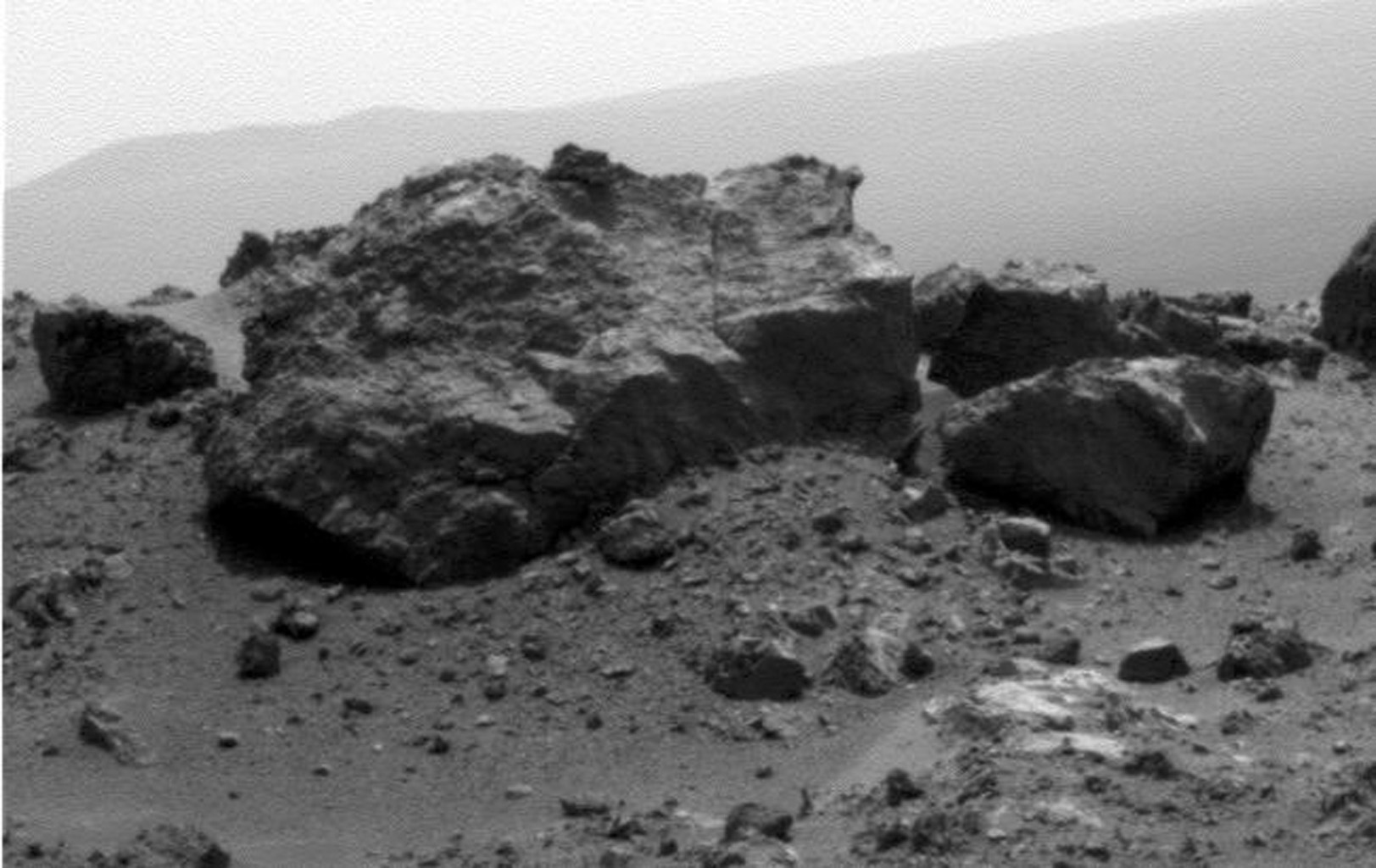 "This view from NASA's Mars Exploration Rover Opportunit is dominated by a rock informally named ""Ridout"" on the northeastern rim of Odyssey. The rock is roughly the same size as the rover, 4.9 feet (1.5 meters) long."