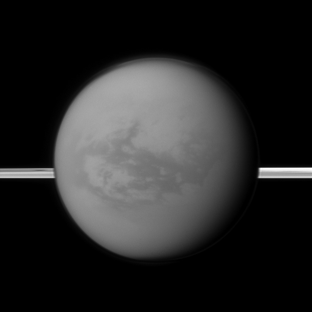 Saturn's rings lie in the distance as NASA's Cassini spacecraft looks toward Titan and its dark region called Shangri-La, east of the landing site of the Huygens Probe.