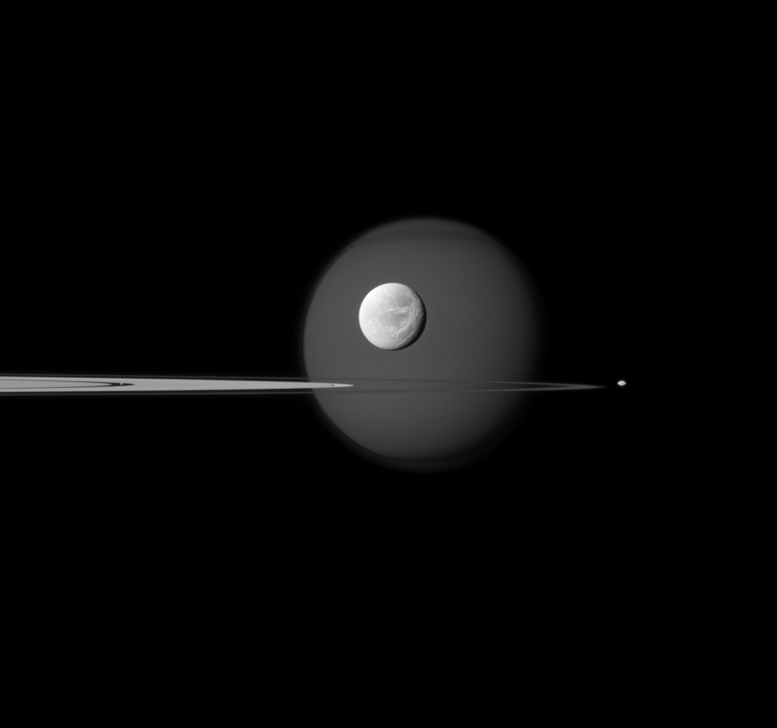 A quartet of Saturn's moons, from tiny to huge, surround and are embedded within the planet's rings in this Cassini composition. Saturn's largest moon, Titan, in the background, and the moon's north polar hood is clearly visible.