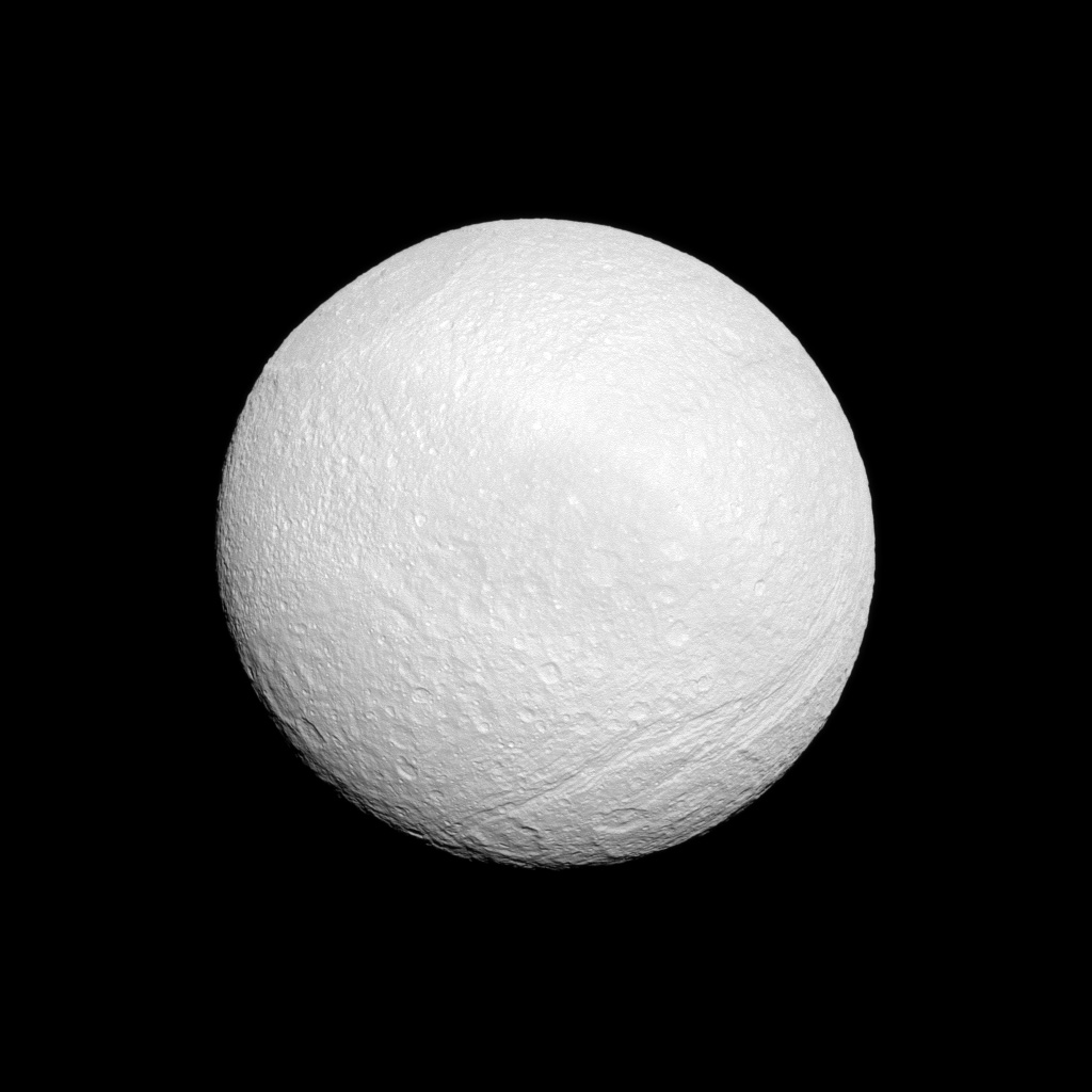 Saturn's moon Tethys shows off its tortured surface in this image from NASA's Cassini spacecraft. At top left of image is huge Odysseus Crater. At bottom right is Ithaca Chasma, a series of scarps that runs north-south across the moon.