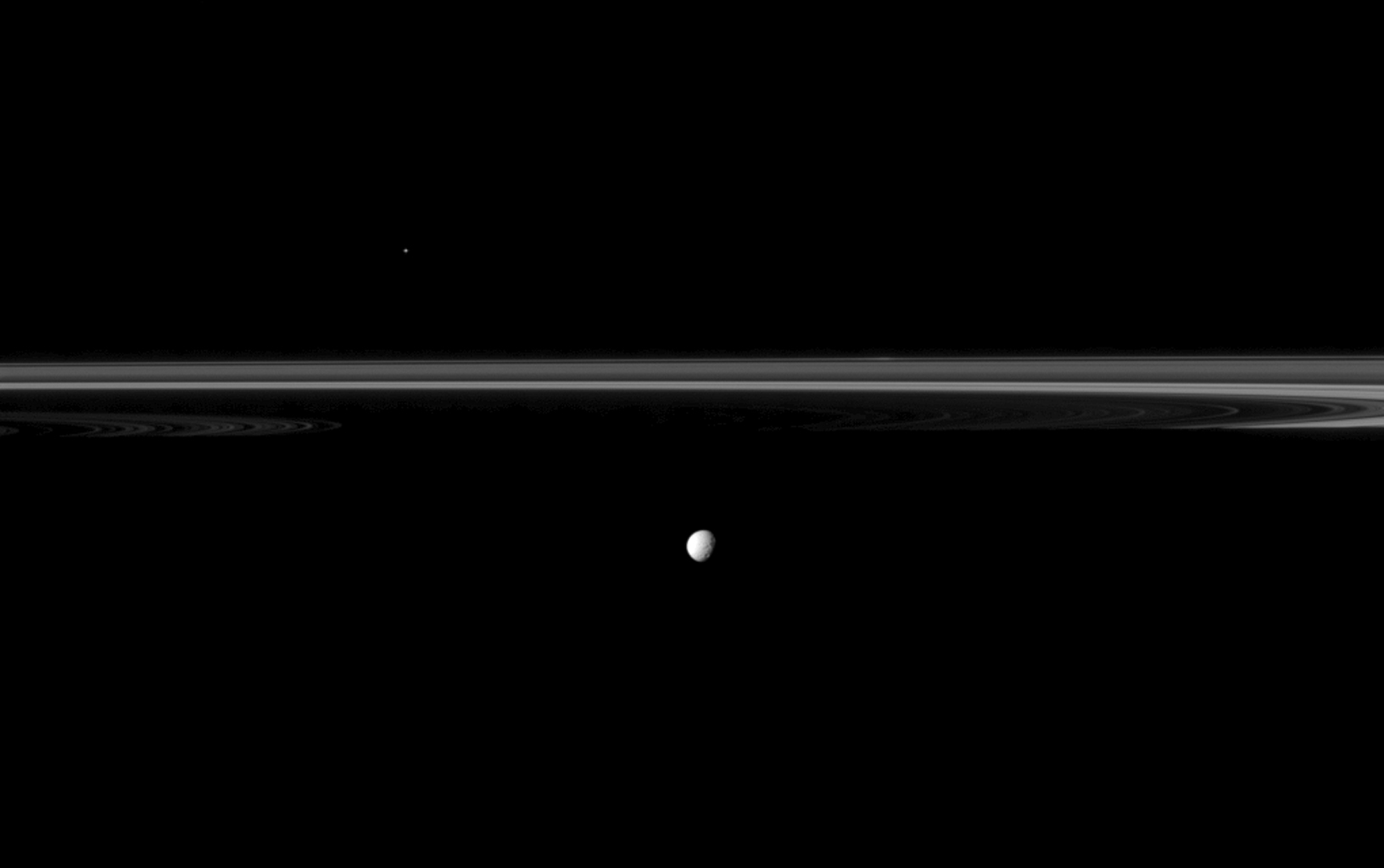 Saturn's moon Mimas joins the planet's rings which appear truncated by the planet's shadow in this image from NASA's Cassini spacecraft.