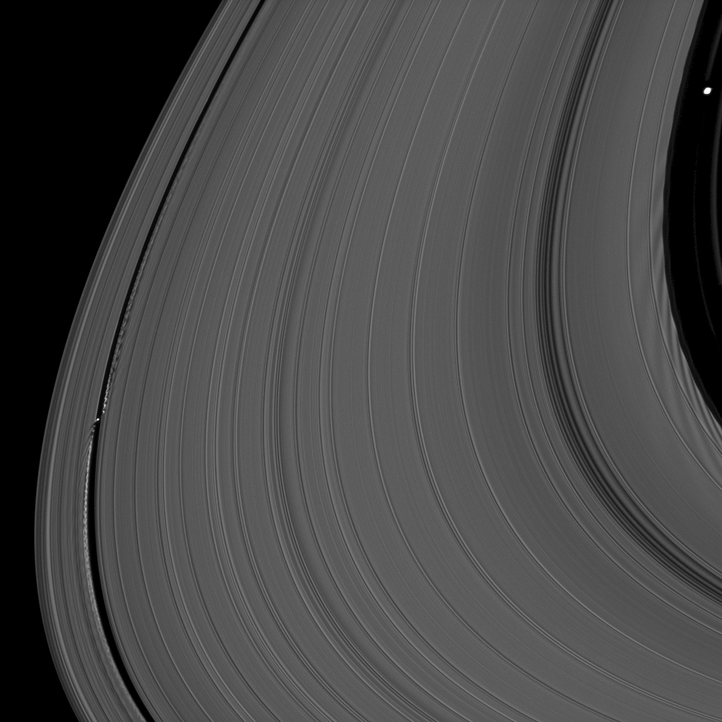 Saturn's moons Daphnis and Pan demonstrate their effects on the planet's rings in this view from NASA's Cassini spacecraft. Daphnis, at left, orbits in the Keeler Gap of the A ring; Pan at right, orbits in the Encke Gap of the A ring.