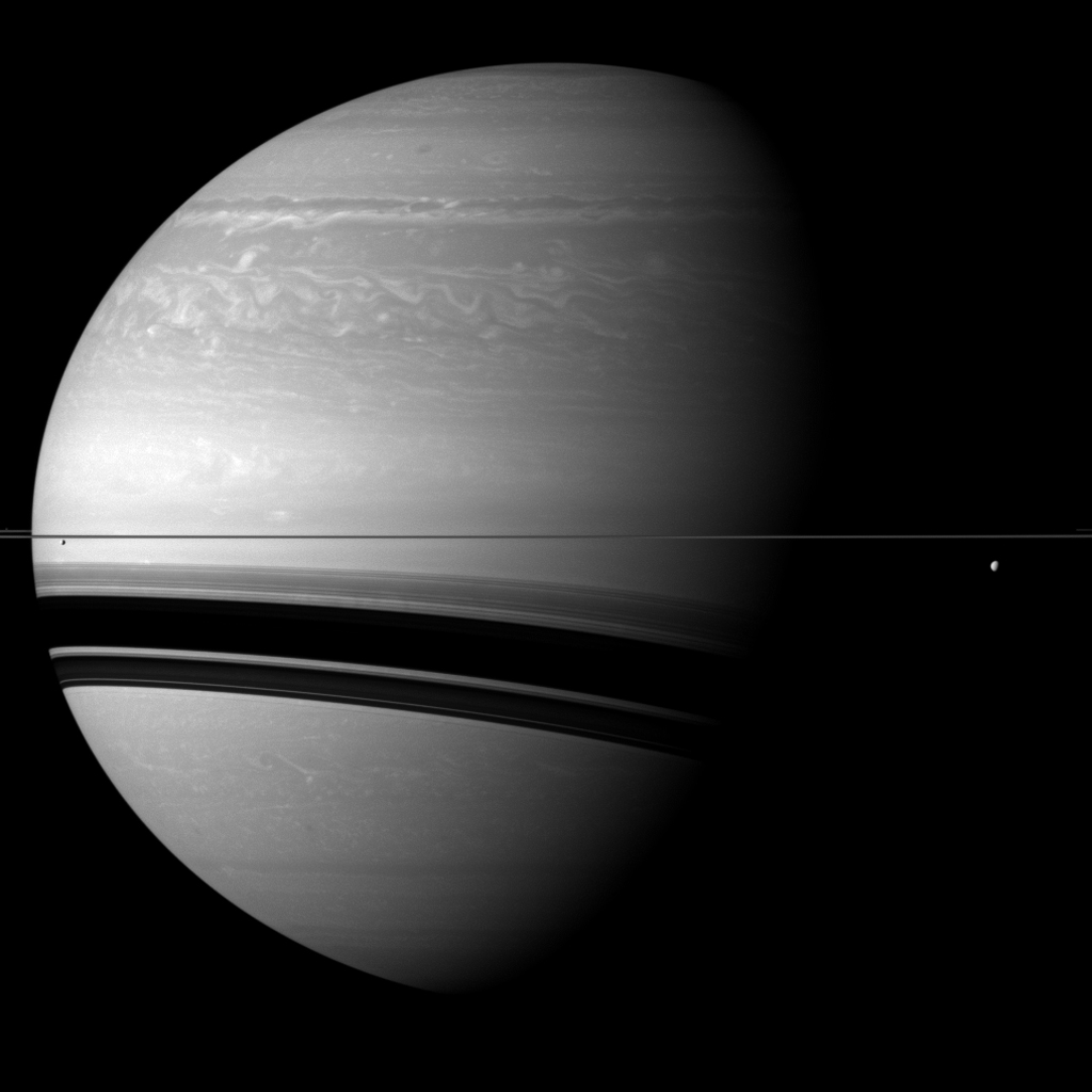 Compared to the gas giant, the two moons shown on either side of Saturn seem particularly small in this view from NASA's Cassini spacecraft. Tethys and Pandora are also present but barely visible.