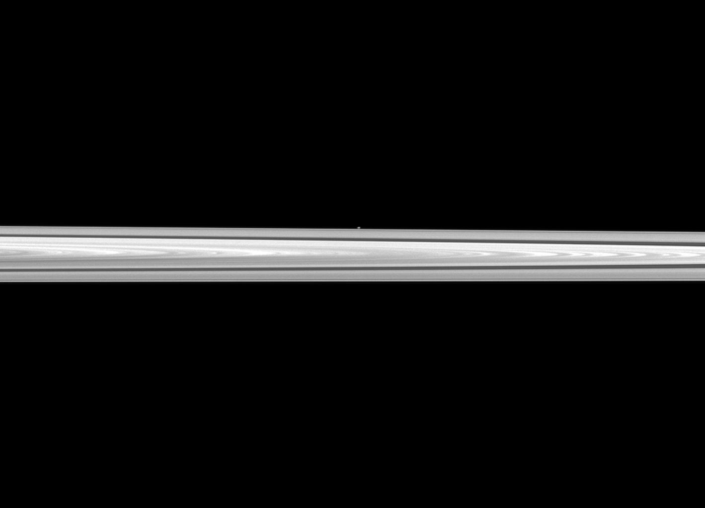 NASA's Cassini spacecraft looks past Saturn's main rings to spy the tiny moon Atlas, which orbits between the main rings and the thin F ring. The main rings are closer to the spacecraft than Atlas is, and the moon appears as only a small, white dot.
