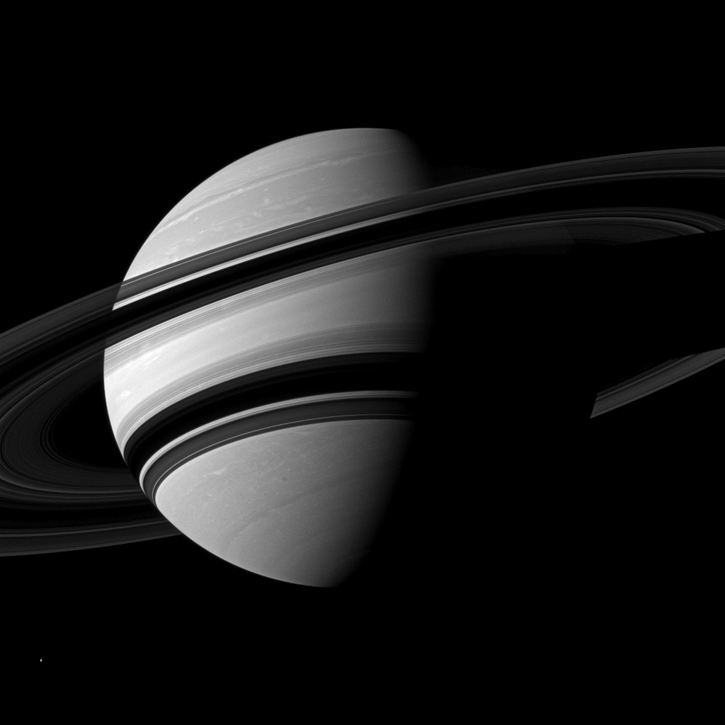 The Cassini spacecraft takes an angled view toward Saturn, showing the southern reaches of the planet with the rings on a dramatic diagonal. The moon Enceladus appears as a small, bright speck in the lower left of the image.