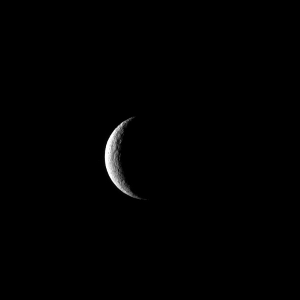 NASA's Cassini spacecraft captures Saturn's moon Rhea at crescent phase, a view never visible from Earth. Near the terminator, a few of Rhea's many craters show up in sharp relief.