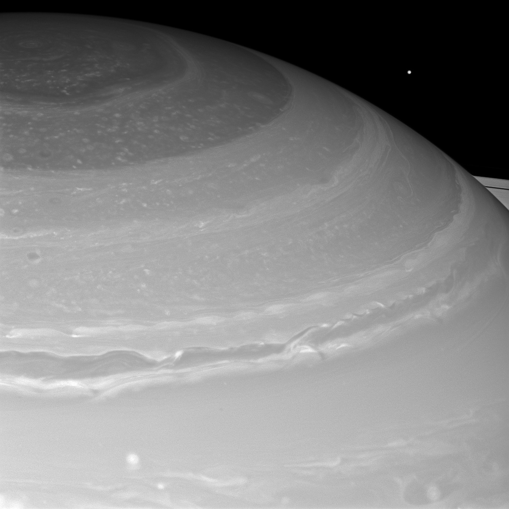 Saturn and its north polar hexagon dwarf Mimas as the moon peeks over the planet's limb. Saturn's A ring also makes an appearance on the far right. Mimas is 246 miles (396 kilometers) across.