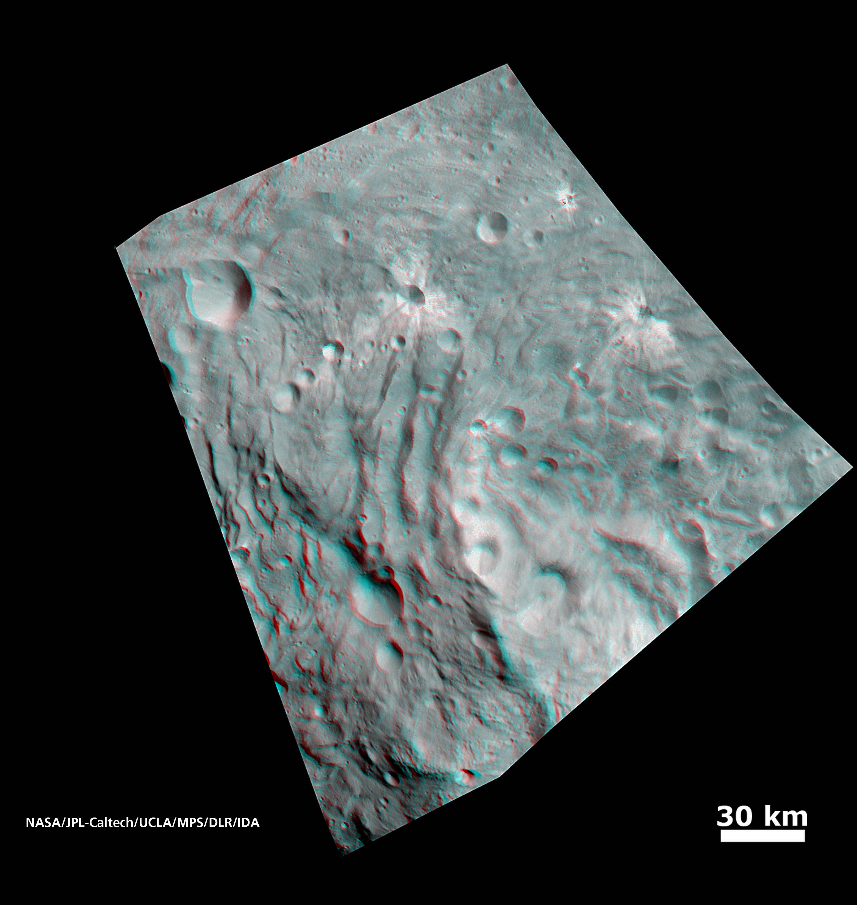 In this image, obtained by NASA's Dawn spacecraft from above the surface of the giant asteroid Vesta, topography in the area surrounding the south pole area shows impact craters, ridges and grooves. You need 3-D glasses to view this image.