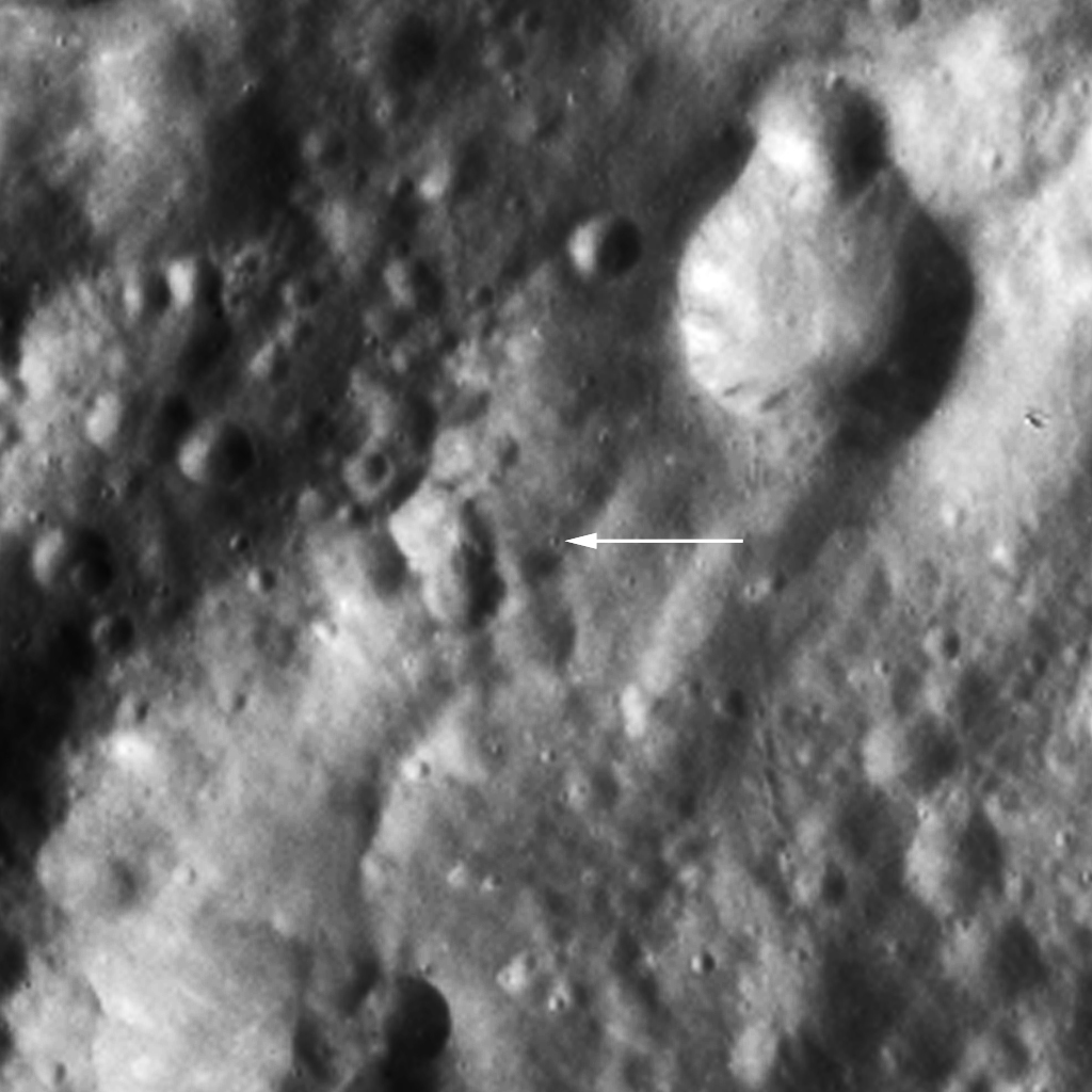 The image shows Claudia (arrow), a tiny crater through which by definition Vesta's prime meridian runs from the asteroid's north pole to its south pole. This image is from NASA's Dawn spacecraft.