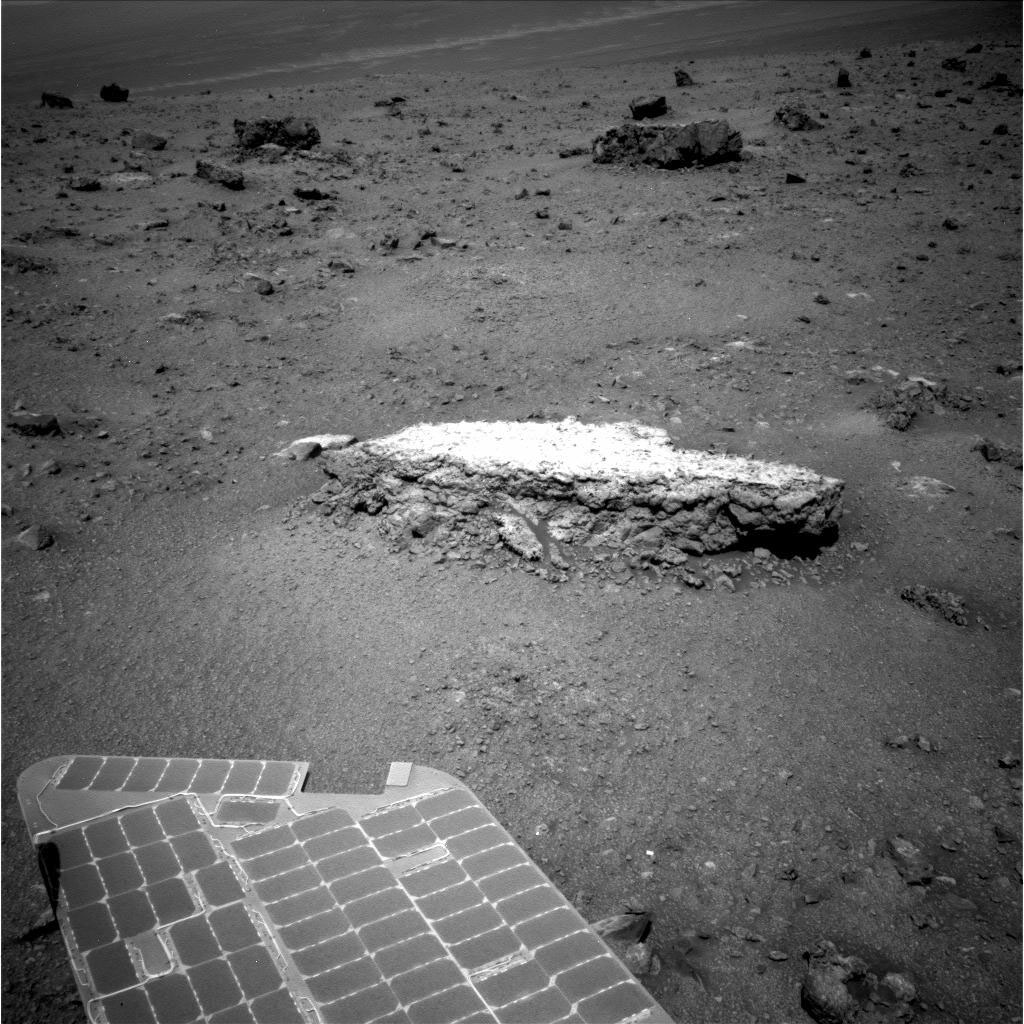 "Part of NASA's Mars Exploration Rover Opportunity's array of photovoltaic cells is visible in the foreground of this image. Opportunity took this picture showing a light-toned rock, ""Tisdale 2,"" on sol 2,690 (Aug. 18, 2011)."