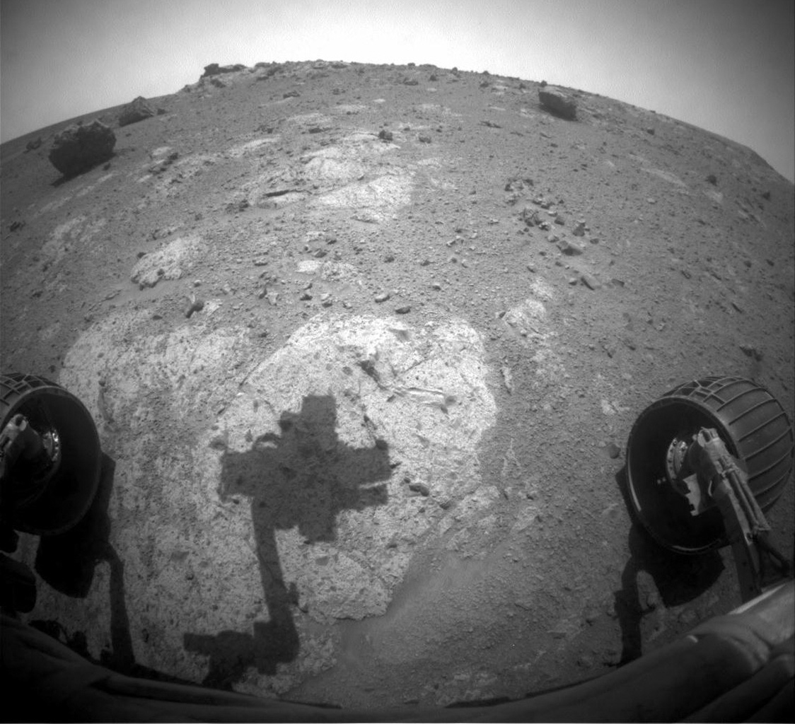 The robotic arm of NASA's Mars Exploration Rover Opportunity casts a shadow on a rock outcrop called 'Chester Lake.' The rock is on a low ridge called 'Cape York,' which is a segment of the western rim of Endeavour crater.