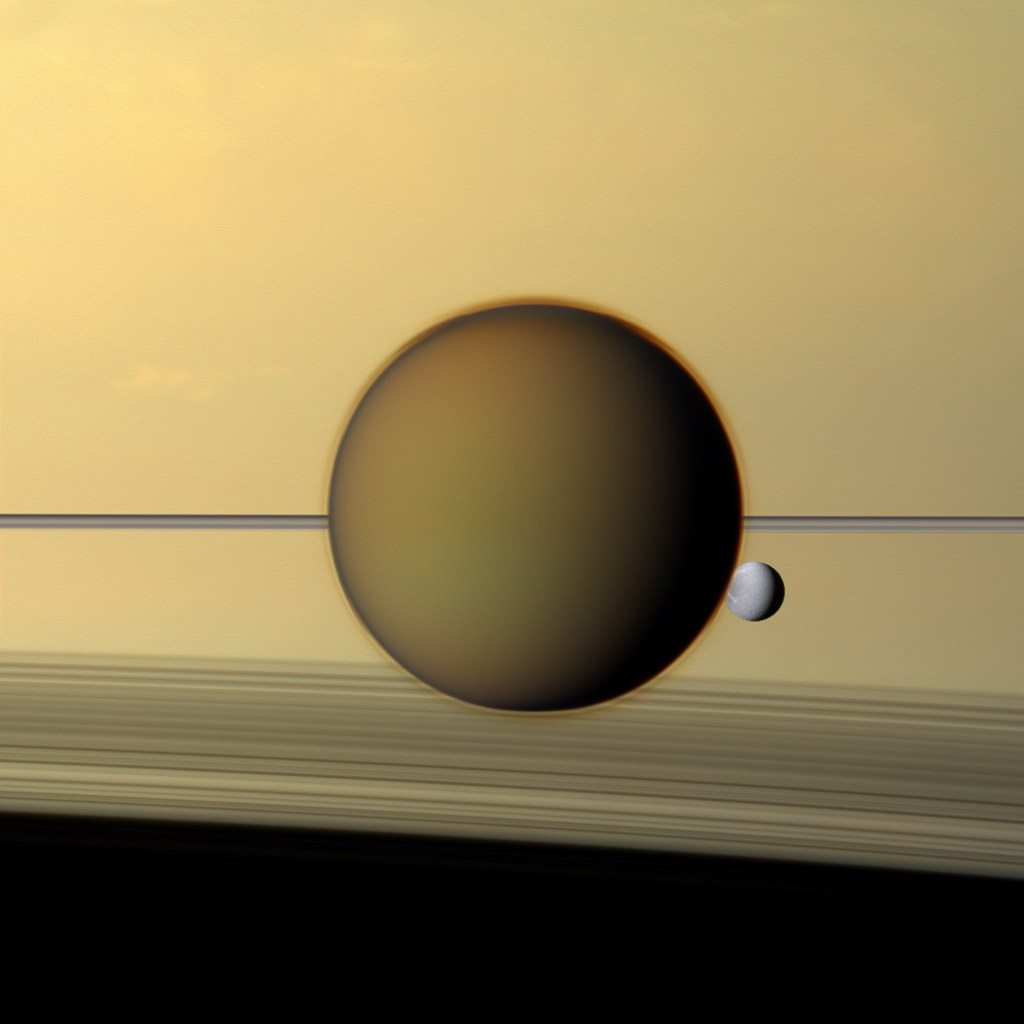 Saturn's fourth-largest moon, Dione, can be seen through the haze of the planet's largest moon, Titan, in this view of the two posing before the planet and its rings from NASA's Cassini spacecraft.