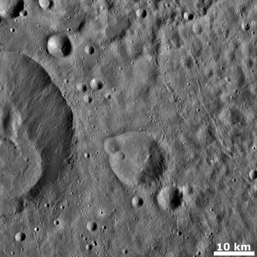This image from NASA's Dawn spacecraft shows numerous grooves (linear depressions) and crater chains, especially in the right hand side of the image of asteroid Vesta.