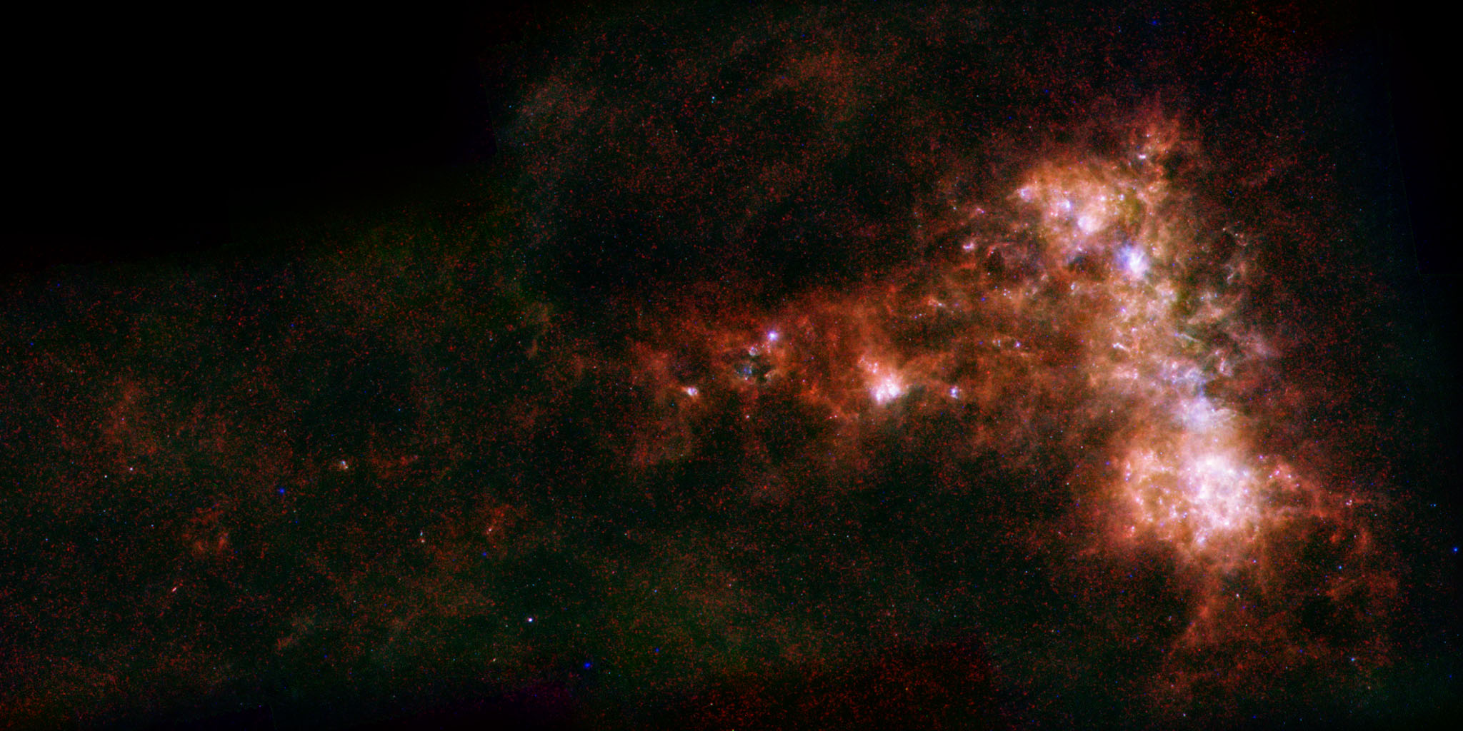 In combined data from ESA's Herschel and NASA's Spitzer telescopes, irregular distribution of dust in the Small Magellanic Cloud becomes clear. A stream of dust extends to left, known as the galaxy's 'wing,' and a bar of star formation appears to right.