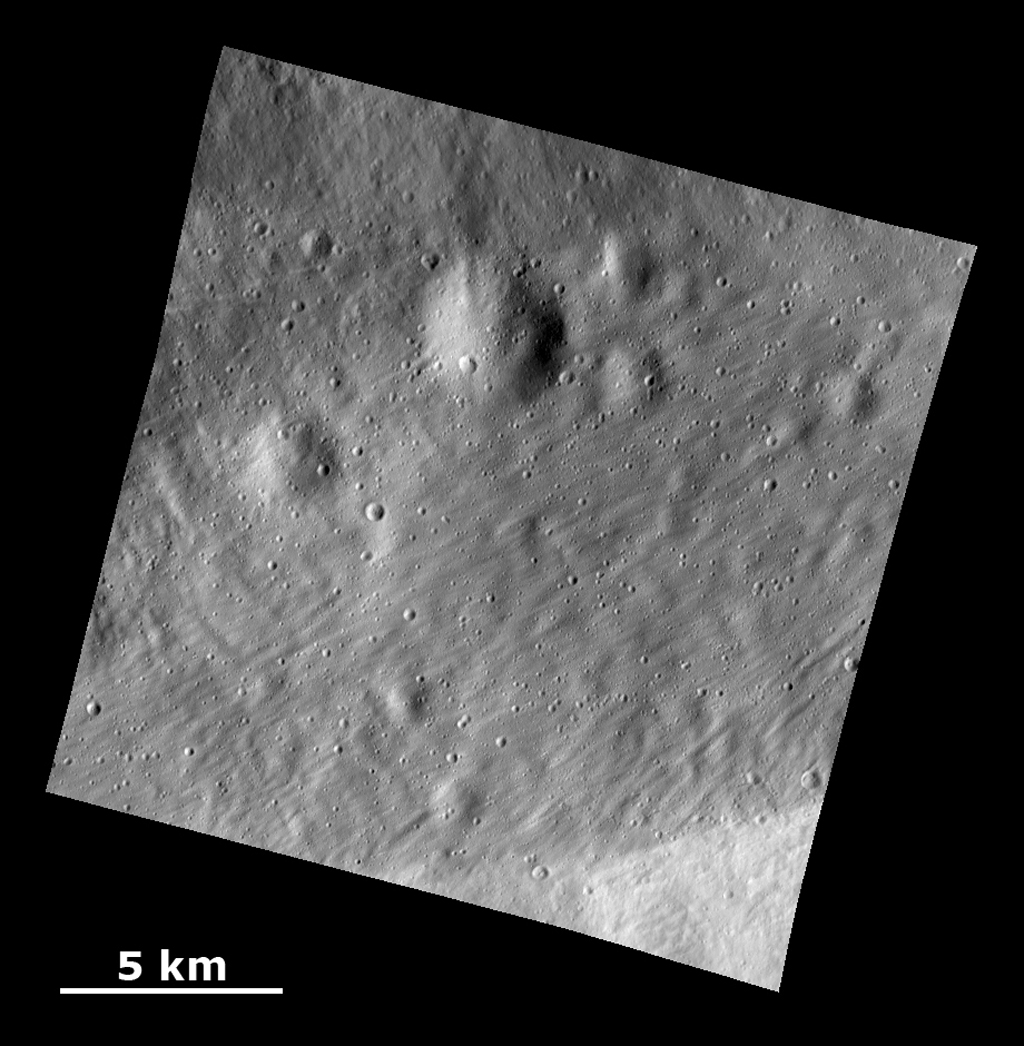 This image from NASA's Dawn spacecraft shows a surface with craters buried under thick ejected material that displays a grooved texture on the giant asteroid Vesta.
