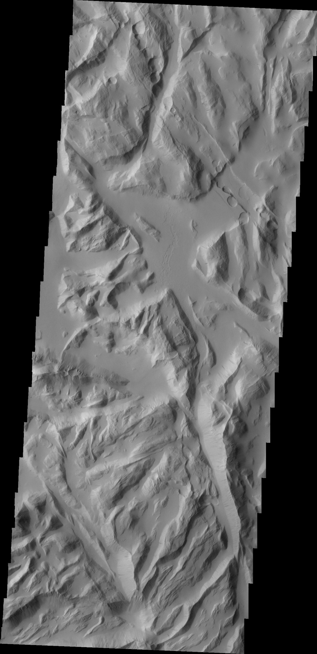 This image captured by NASA's 2001 Mars Odyssey spacecraft shows part of Sulci Gordii, a complexly fractured region east of Olympus Mons.