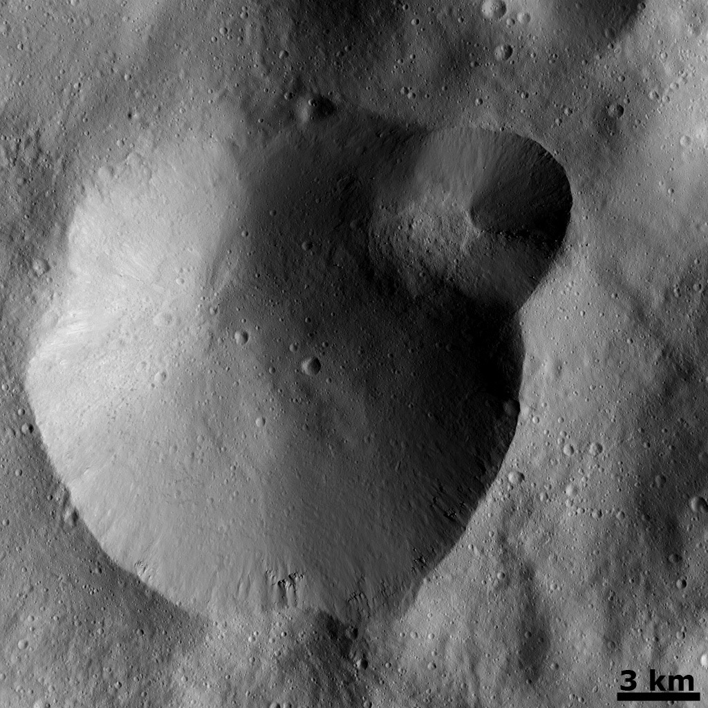 This image from NASA's Dawn spacecraft shows two overlapping impact craters on asteroid Vesta. The rims of the craters are both reasonably fresh but the larger crater must be older because the smaller crater cuts across the larger crater's rim.