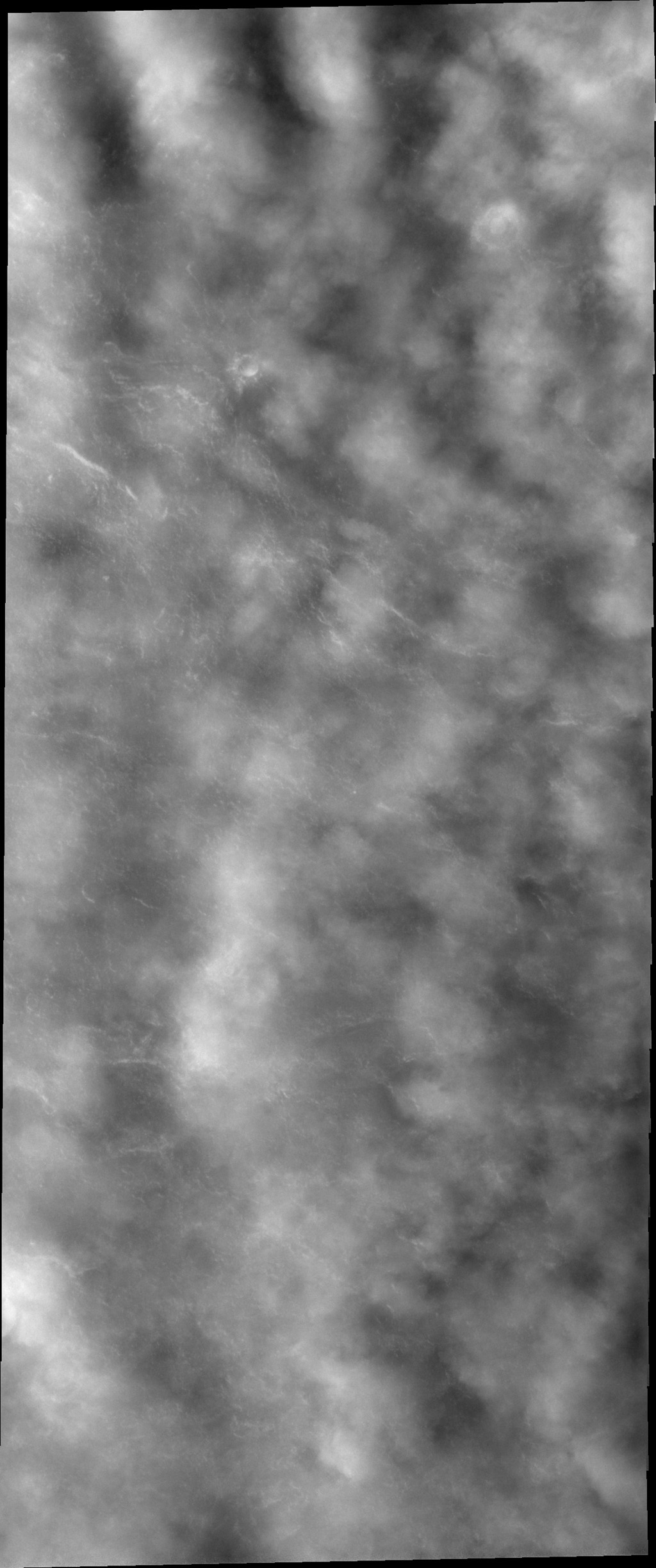 With the changing of seasons comes changes in weather. This image from NASA's 2001 Mars Odyssey spacecraft shows clouds in the north polar region. The surface is just barely visible in part of the image.