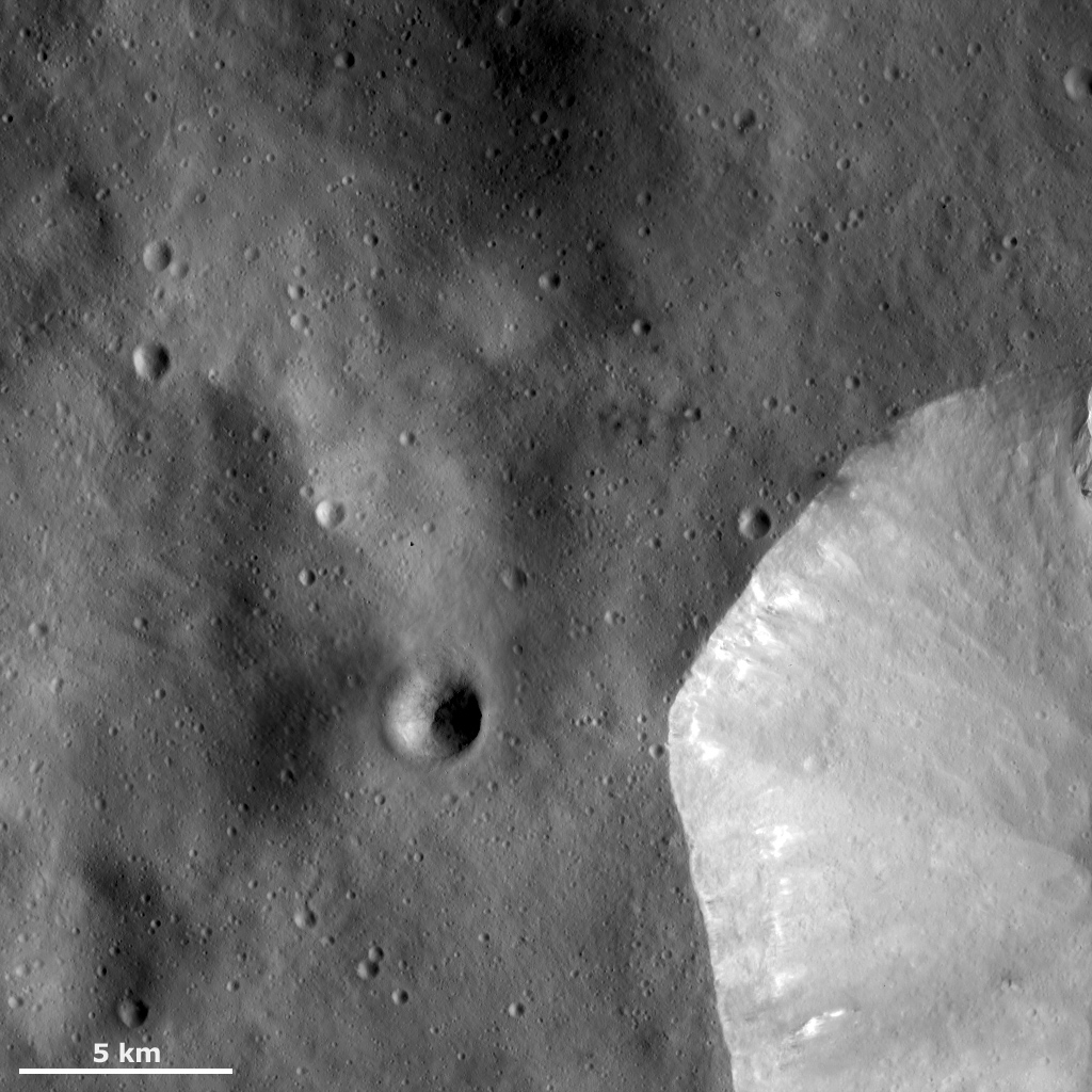 This image from NASA's Dawn spacecraft shows a sharp, fresh crater rim of a large crater that is only partly in the bottom right corner of this image and is located in Vesta's Numisia quadrangle, near asteroid Vesta's equator.