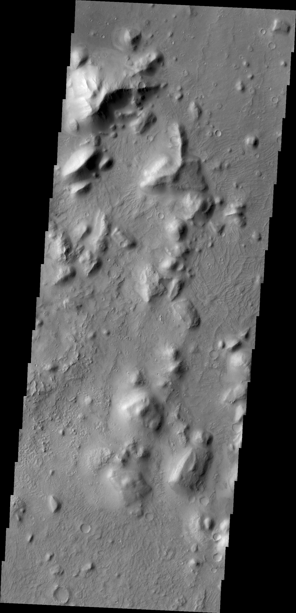 Between the highlands of Terra Cimmeria and the low plains of Elysium Planitia and Nepenthes Planum lies the rugged region called Nepenthes Mensae as seen by NASA's 2001 Mars Odyssey spacecraft.