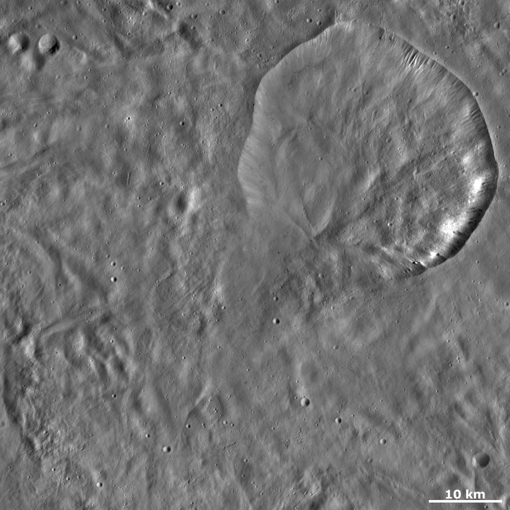 This image from NASA's Dawn spacecraft of asteroid Vesta shows Aquilia crater located in Pinaria quadrangle, in Vesta's southern hemisphere. The especially degraded bottom rim was probably formed by debris slumping into the crater.