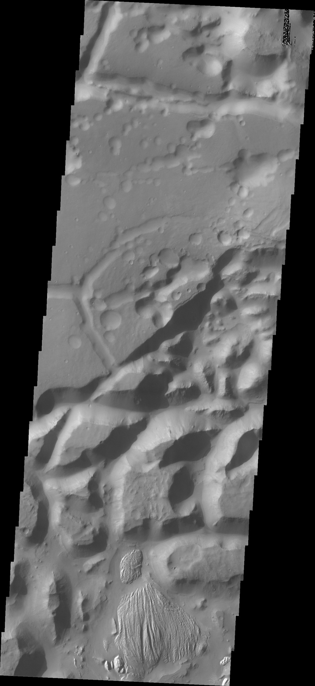 The isolated mesas in this image from NASA's 2001 Mars Odyssey spacecraft are part of Arsinoes Chaos. There is a material that differs from the rest of the chaos visible at the bottom of the image.