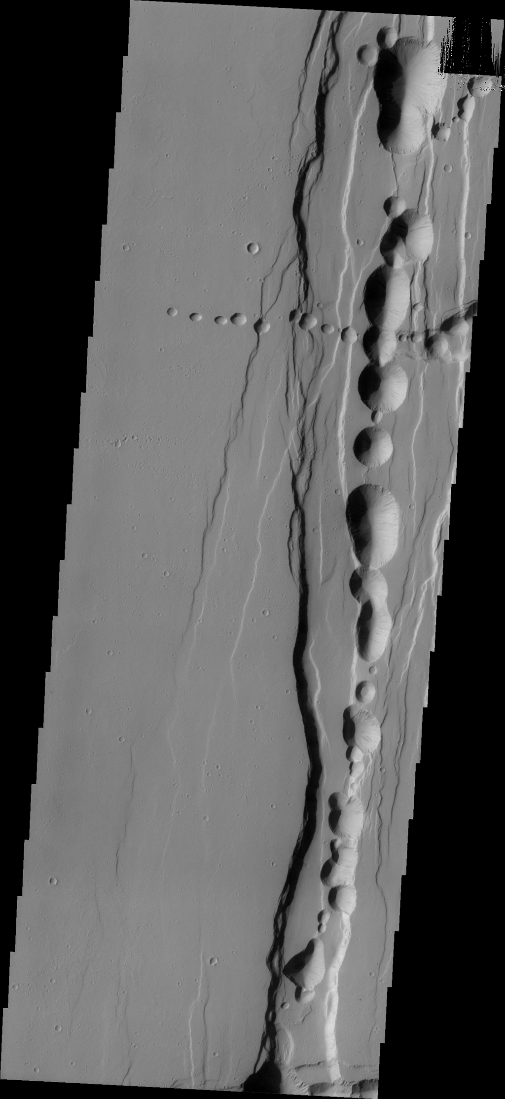 Tractus Catena is a series of collapse pits and fractures south of Alba Mons as seen in this image from NASA's 2001 Mars Odyssey spacecraft. The collapse pits, which run in two directions in this image, are typically indicative of volcanic lava tubes.