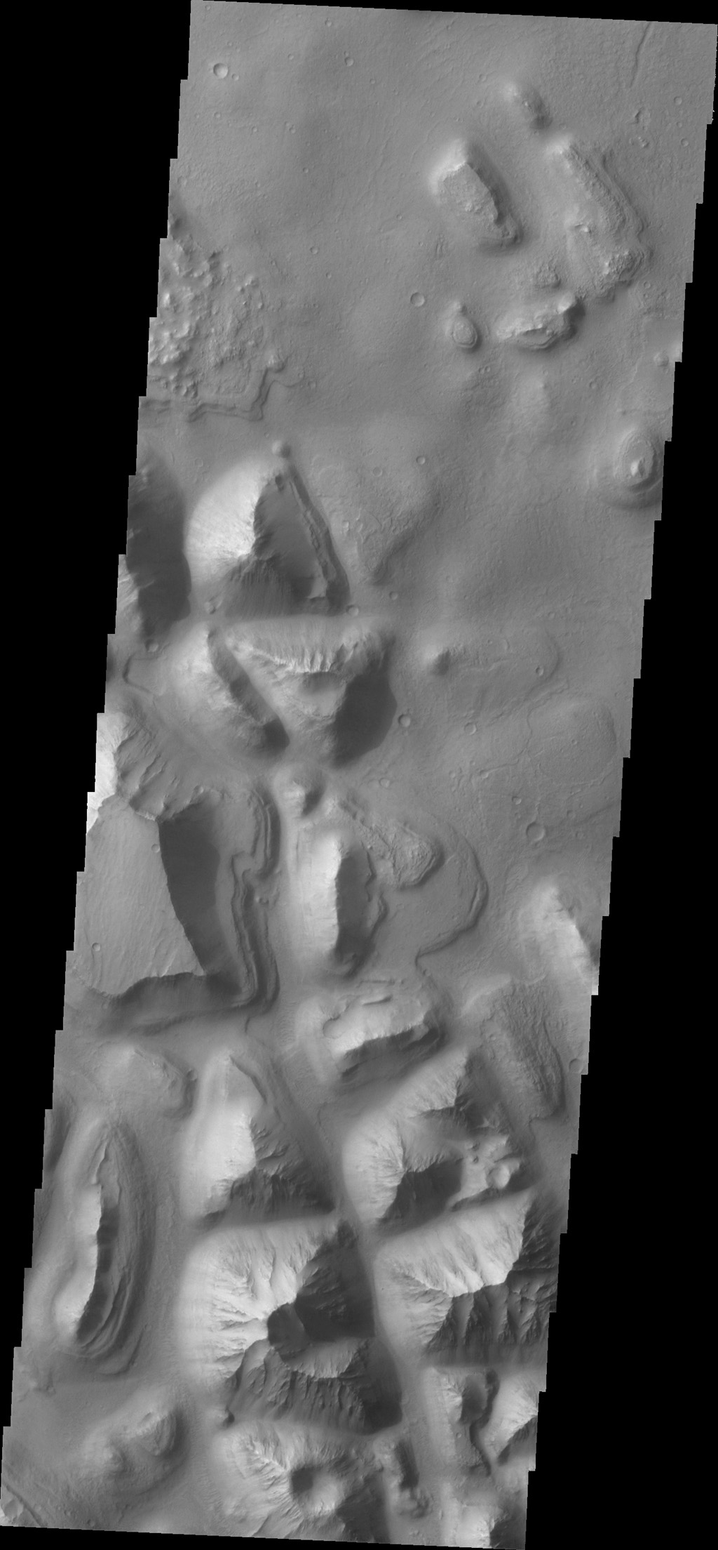 This image from NASA's 2001 Mars Odyssey spacecraft shows a portion of Hydraotes Chaos. The individual hills on the left side of the image also appear to be layered.