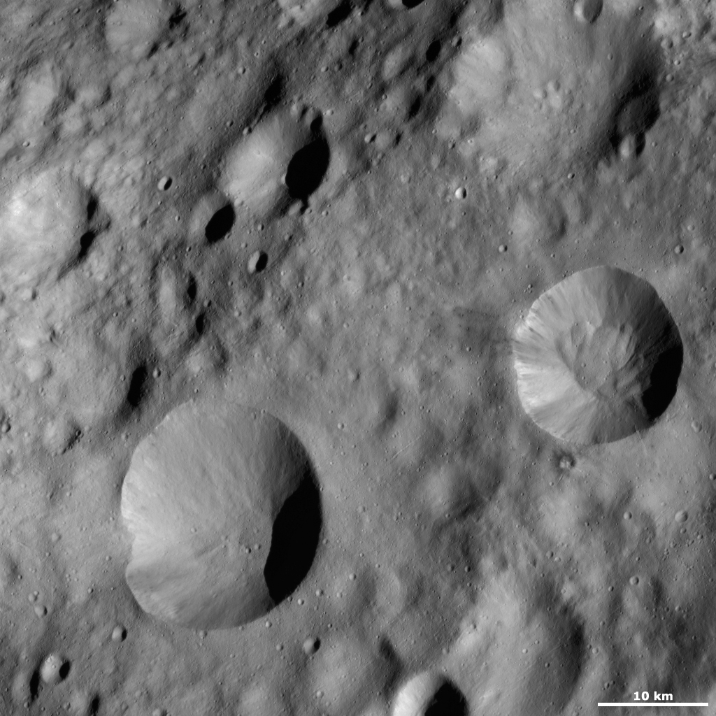 This image from NASA's Dawn spacecraft is located in Lucaria Tholus quadrangle, in Vesta's northern hemisphere. Around Publicia's rim are many alternating streaks of bright and dark material tumbling down towards its center.