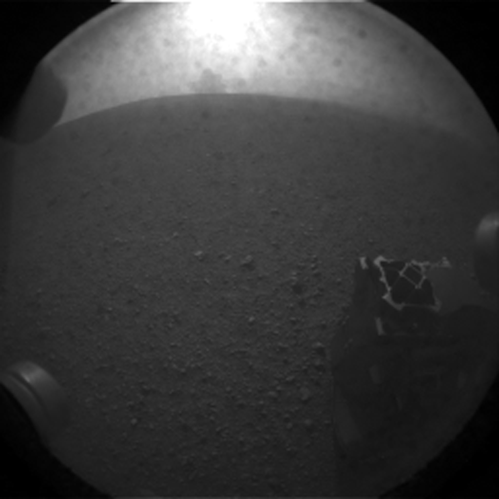 "This is the first image taken by NASA's Curiosity rover, which landed on Mars the evening of Aug. 5 PDT (morning of Aug. 6 EDT). It was taken through a ""fisheye"" wide-angle lens on one of the rover's rear right Hazard-Avoidance cameras."