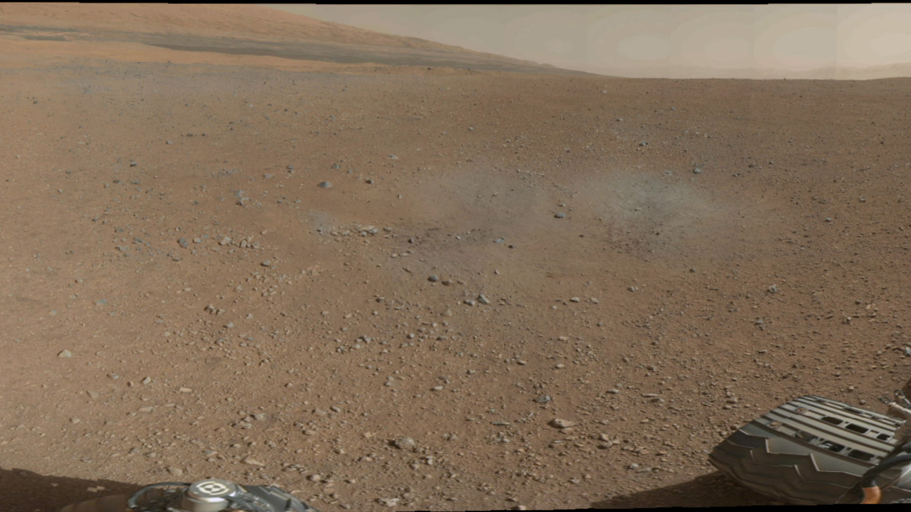 This is a portion of the first color 360-degree panorama from NASA's Curiosity showing the rover's a mountain at the center of Gale Crater called Mount Sharp, can be seen in the distance, to the left, beginning to rise up.