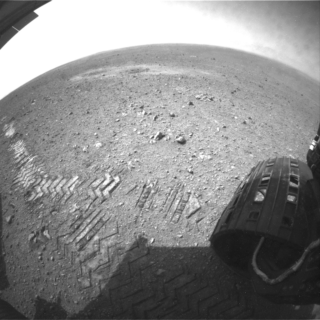 This image shows a close-up of track marks left by NASA's Curiosity rover. Holes in the rover's wheels, seen here in this view, leave imprints in the tracks that can be used to help the rover drive more accurately. The imprint is Morse code for JPL.