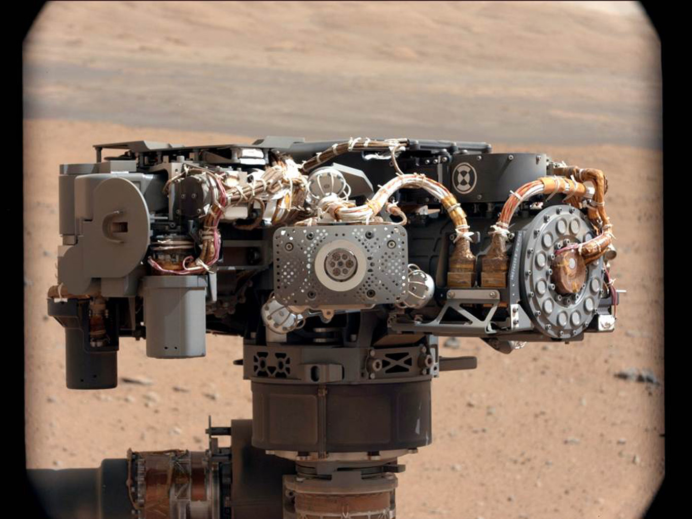This image shows the Alpha Particle X-Ray Spectrometer (APXS) on NASA's Curiosity rover, with the Martian landscape in the background. This image let researchers know that the APXS instrument had not become caked with dust during Curiosity's landing.