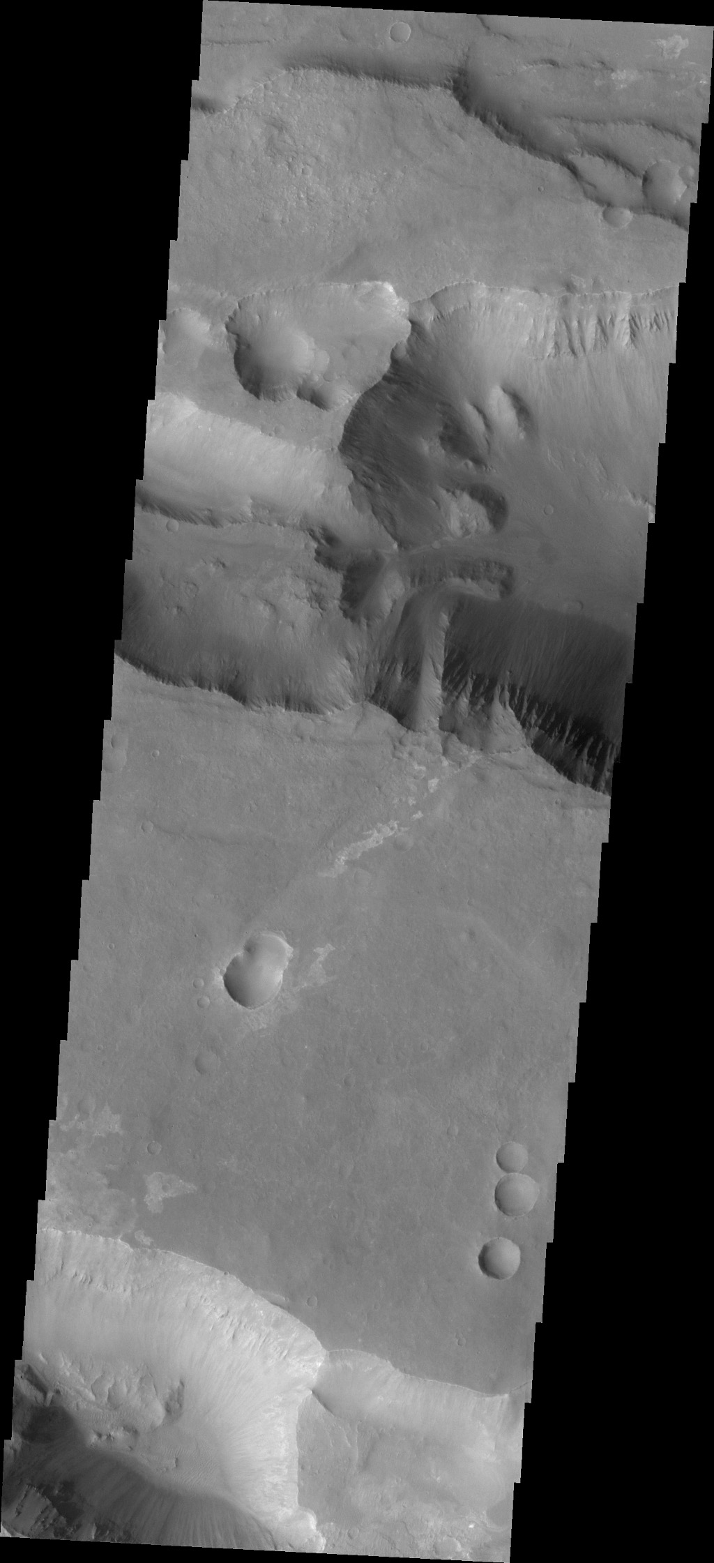 This image captured by NASA's 2001 Mars Odyssey spacecraft shows a portion of Coprates Catena, a shallow system of connecting depressions south of Coprates Chasma.