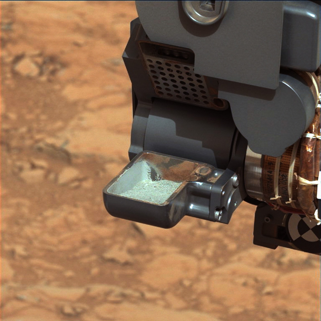 NASA's Curiosity rover shows the first sample of powdered rock extracted by the rover's drill. The image was taken after the sample was transferred from the drill to the rover's scoop.