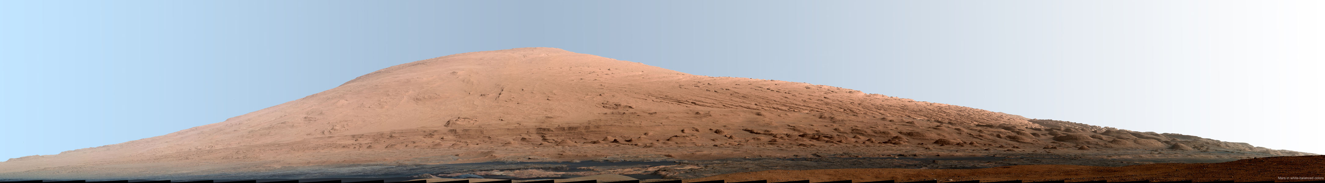 This mosaic of images from the Mast Camera (Mastcam) on NASA's Mars rover Curiosity shows Mount Sharp in a white-balanced color adjustment that makes the sky look overly blue but shows the terrain as if under Earth-like lighting.