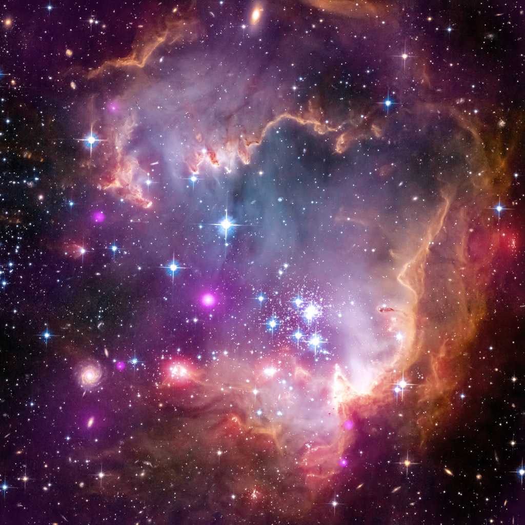The tip of the 'wing' of the Small Magellanic Cloud galaxy is dazzling in this new view from NASA's Great Observatories. The SMC, is a small galaxy about 200,000 light-years way that orbits our own Milky Way spiral galaxy.