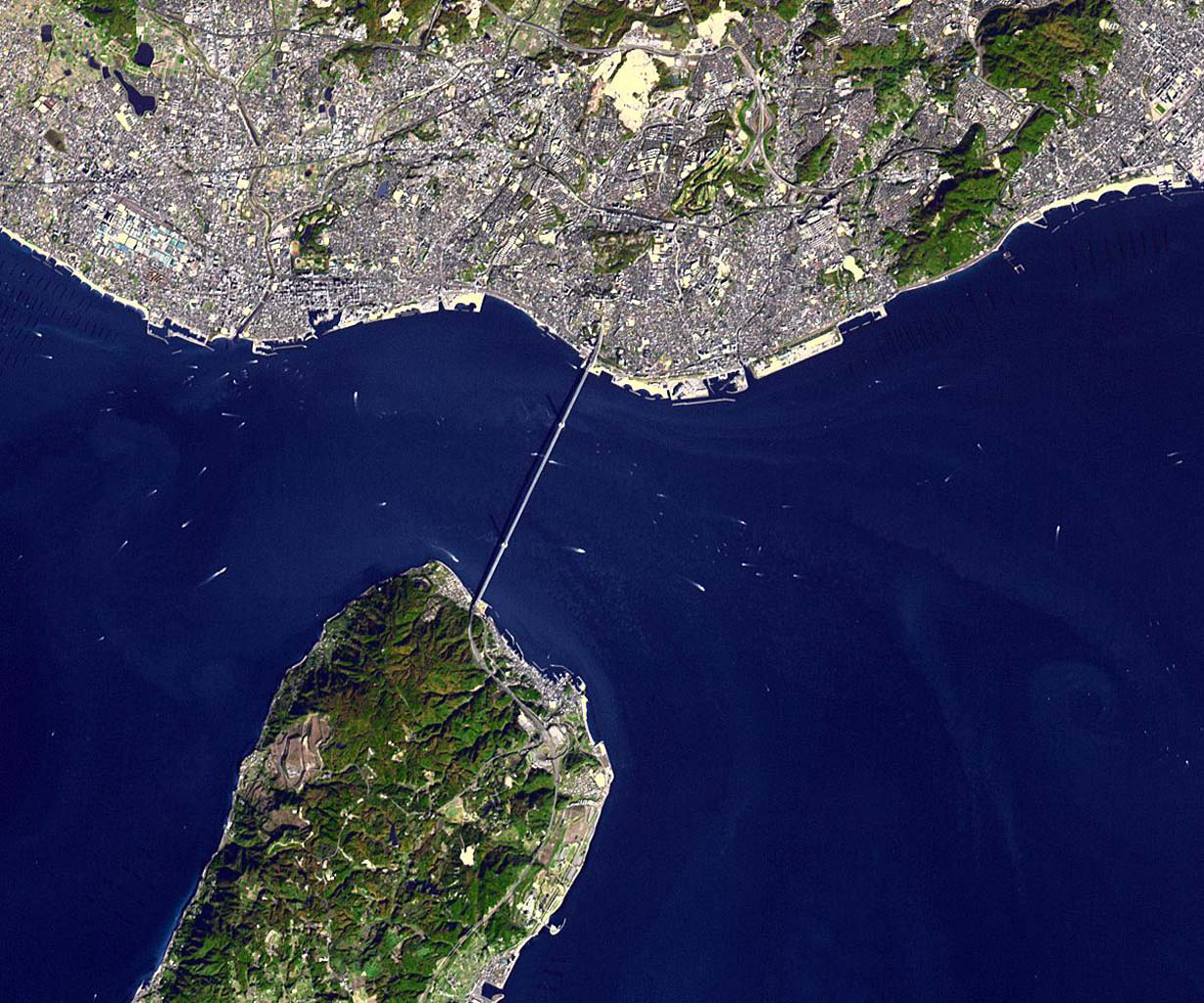NASA's Terra spacecraft shows the Akashi Kaikyo Bridge (or Pearl Bridge), the longest central span of any suspension bridge in the world, at 1991 meters, connecting the city of Kobe, Japan with Iwaja on Awaji Island by crossing the busy Akashi Strait.